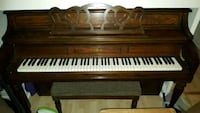 brown and white upright piano 24 km
