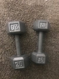 two unpaired 20 lbs and 15 lbs gray dumbbells