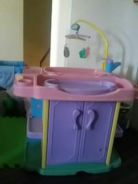 pink, purple, and yellow plastic sink cabinet toy with crib mobile