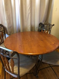 Oval brown wooden dining table with four chairs