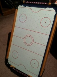 white and black mini air hockey table