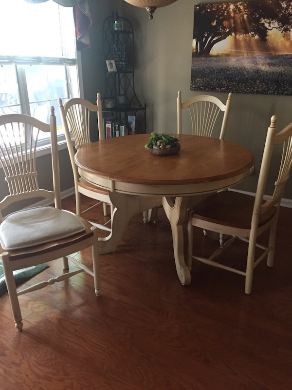 French white wooden kitchen table with 4 chairs. Self-storing middle leaf  in table. Measures 47 inches round and 18 inch extra leaf self stored in ...