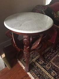 "Beautiful marble top round side table 30""diameter 36""H gracefully carved legs with winged figurine motif.  Bottom has a small round shelf underneath Berwyn Heights, 20740"
