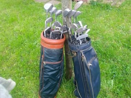 2 blue and black golf bag with golf clubs