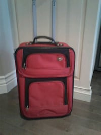 Red american tourister carry on with extendable handle on wheels