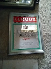 Gray wooden frame mirror with liquor brand stamp