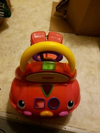 red and yellow Fisher-Price shape sorter ride-on car