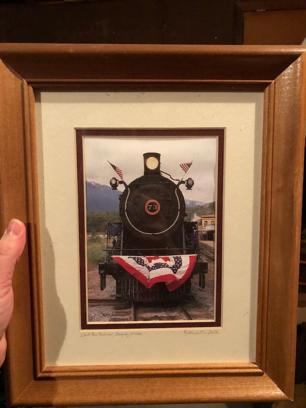 black steam train photo and brown wooden frame