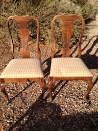 Two matching high back chairs with cloth seats.