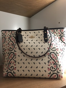 white, black, and red floral leather tote bag
