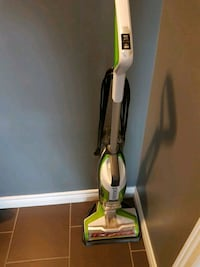green and gray upright vacuum cleaner