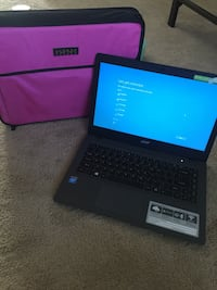 black Acer laptop with purple laptop sleeve