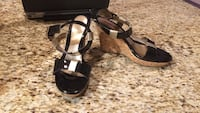 pair of black-and-brown leather open-toe ankle strap wedge sandals