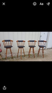 four brown and black wooden bar stools