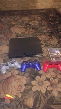black Sony PS3 slim with two controllers
