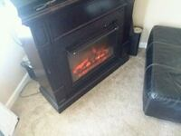 black wooden fireplace. Elect heater with remote Pevely