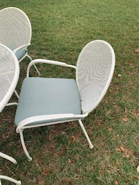 White 5ft round outdoor table and 6 chairs with cushions. Has the umbrella base, but not the umbrella. Aldie