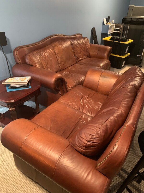 Brown leather sofa and love seat with wooden framed glass top coffee table and two matching end tables.