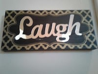 brown and black laugh wall decor