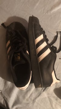 Pair of black adidas superstar shoes