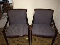two brown wooden framed dark blue padded armchairs