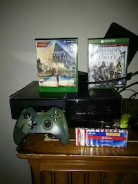 black Xbox One console with controller and game ca