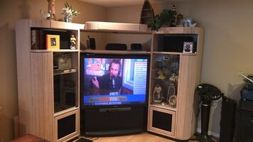 Beige wooden tv hutch with black rear-projection tv