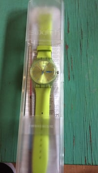 Round gold analog watch with green leather strap