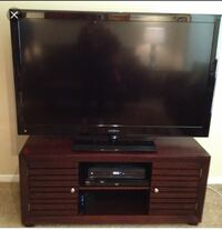 flat screen television with brown wooden TV stand null