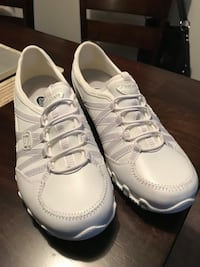 pair of white Skechers office shoes