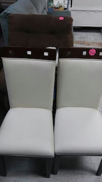 two white leather parson chairs