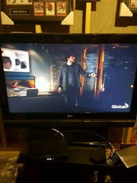 black flat screen TV with brown wooden TV stand Edmonton, T5W