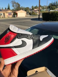unpaired red, white, and black Nike Air Jordan 1 shoe