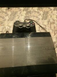 black Sony PS3 super slim console with controller
