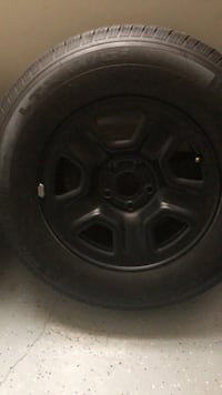 Black 5-spoke car wheel with tire