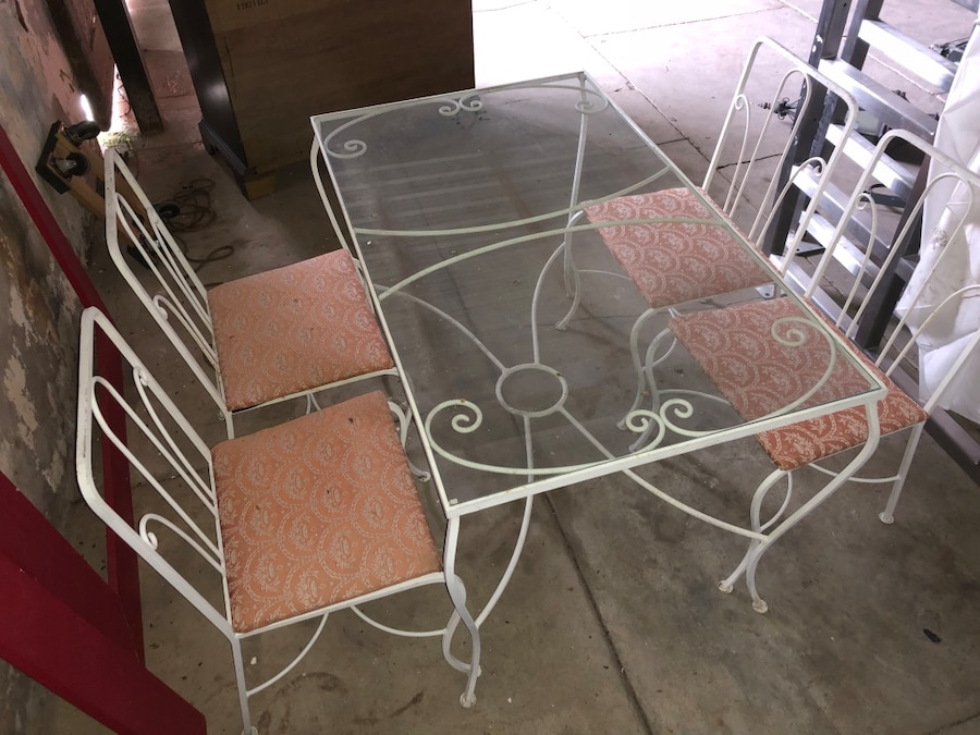 Photo White metal patio table with glass top and 4 chairs.