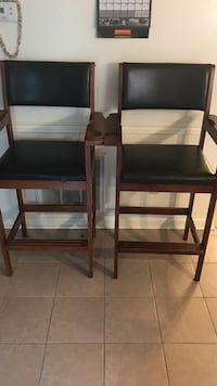 Two black leather armchairs with brown wooden frames