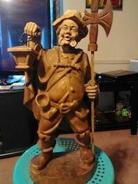 brown wooden sculpture of man holding lantern