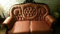 brown wooden framed white leather padded sofa