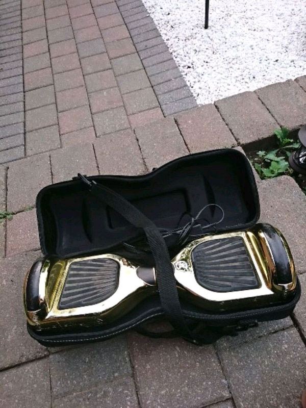 gold and black self-balancing board with case