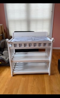 White wooden changing table with changing pad and Chevron liner