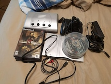 grey Sony PS2 console with game discs and controller
