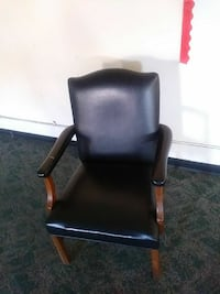 black leather padded brown wooden armchair