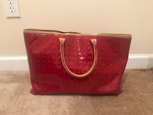 Red leather tote bag with tassel