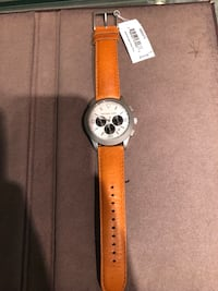 Round silver analog watch with brown leather strap 591 km