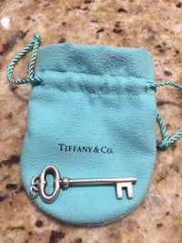 silver-colored skeleton key with teal Tiffanu & Co. dust bag