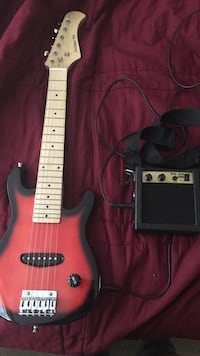 Red and black electric guitar with guitar amplifier Derry, 03038