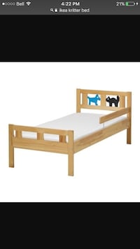 brown wooden toddler bed with white mattress
