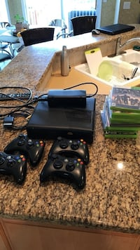 black Xbox 360 console with controllers and game cases