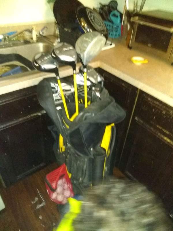 Acuity yellow and black golfclub set and red net bag full of  golfball 727577f6-efea-4307-9d20-04ad159257d3
